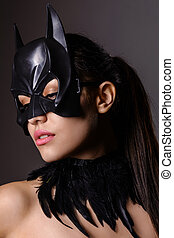 Portrait of charming brunette girl in Batman mask on a gray...