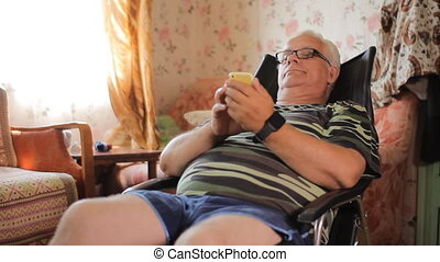 Senior man sitting with a phone in a leather chair at home....