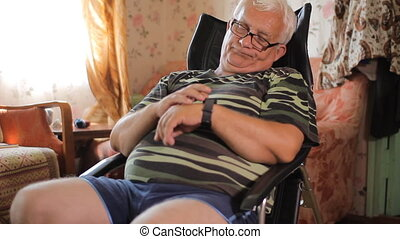 Senior man sits with smart clock in a leather chair near the house TV. A man looks at the message by a smart watches