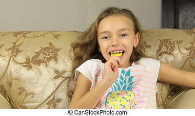 Girl licking candy on a stick in the form of lemon and raises the thumbs up.