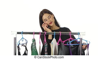 Female customers selecting dresses at the shop and talking on the phone. White