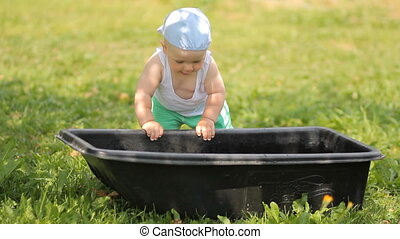 Adorable boy playing with a basin of water in the garden. He gets up and smiles