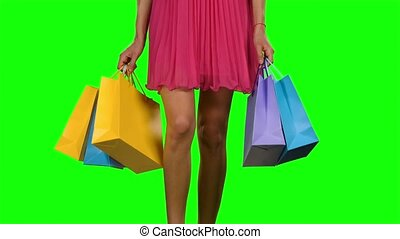 Woman walking and holding shopping bags. Green screen -...