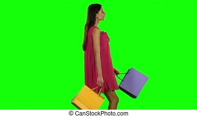 Woman with shopping bags walking Green screen - Woman with...