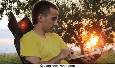 Young man sitting with a laptop in a chair in the garden. During breaks trees orange sun at sunset