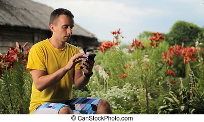 Young man calling on the phone near flowers in the garden. White, red and purple flowers in the background