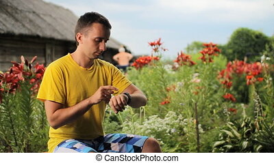 Young man touching smart watch near flowers in the garden. Checks messages against the backdrop of white, red, purple flowers