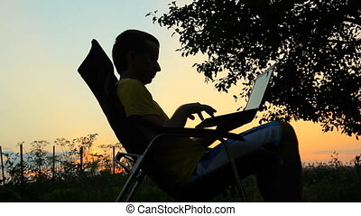 Slhouette of happy business man with laptop working on the field at sunset time. Man swinging on chair