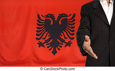 Open hand and Albania flag in the background - Businessman...