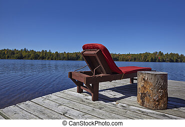 Wooden chairs overlooking a lake on a sunny day