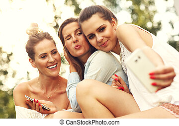 Happy group of friends with smartphones - Picture presenting...