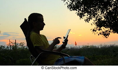Silhouette of male in chair playing in tablet. Against the background of an orange sky after sunset