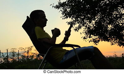 A man sits in a chair with the phone and cup of tea. Against the background of an orange sky after sunset