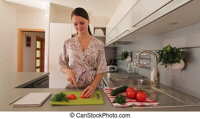 Young woman slicing a vegetable - Young woman in kitchen...