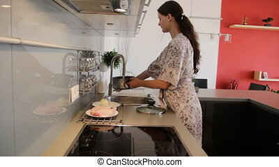 Woman cooking chicken broth - Young woman in the kitchen...