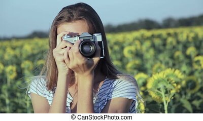 Girl taking photo with an old film camera Handheld shot -...