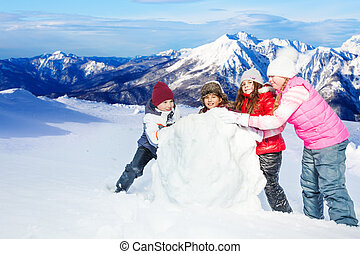 Four happy friends rolling the snowball at winter - Four...