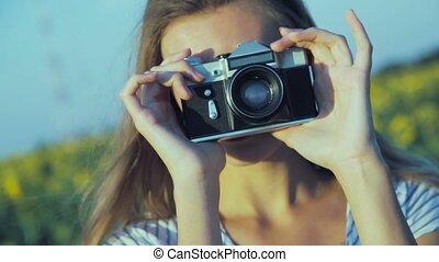 Girl taking photo with an old film camera. Handheld shot. -...