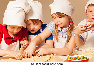 Four young chefs having fun making homemade cookie - Four...