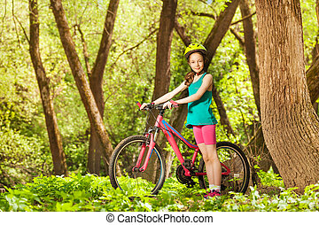 Young girl with her mountain bike in sunny forest