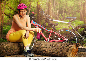 Active woman relaxing after cycling sitting on log