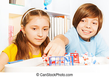 Boy and girl playing ice hockey table board game - Two kids,...