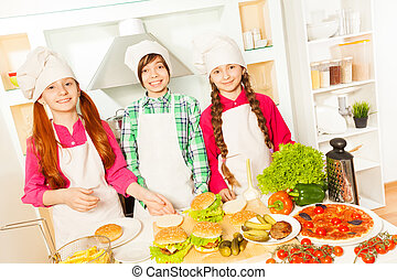 Three friends preparing hamburgers in the kitchen - Three...