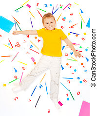 Boy laying among office supply objects collection