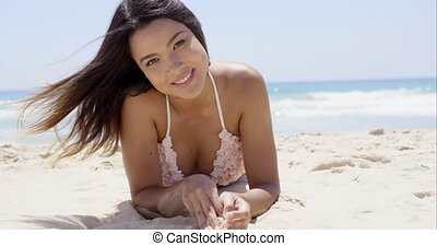 Sexy brunette girl laying on sandy beach and smiling to the...