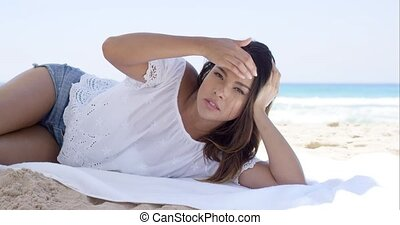 Young woman relaxing on a towel on the beach - Attractive...