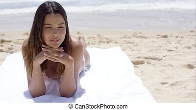Pensive young woman sunbathing on a beach lying on her towel...