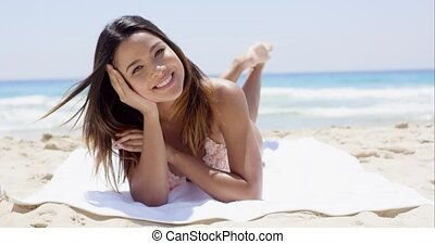 Gorgeous young woman with a lovely smile lying sunbathing on...