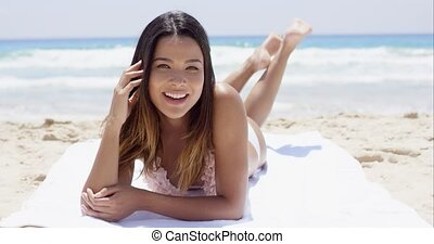 laughing happy young woman sunbathing on a beach in her...