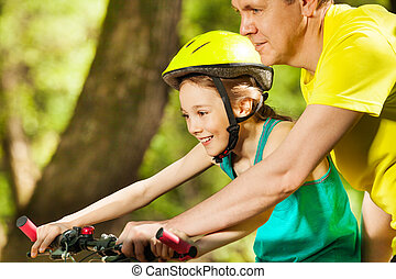 Smiling girl learning to ride with her father