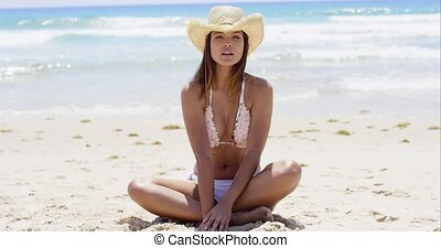 Thoughtful young woman in a bikini sitting cross-legged on a...