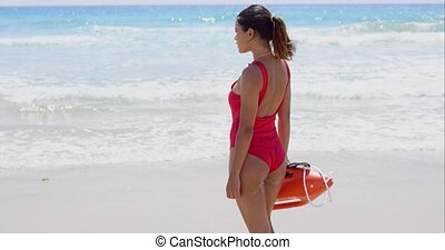 Rear view on lifeguard in red with buoy - Rear view on...