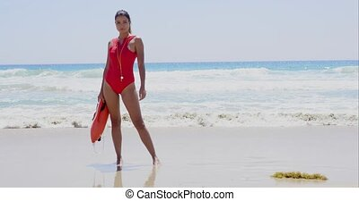 Beautiful lifeguard wearing red swim suit stands with rescue...