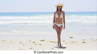 Shapely young woman in a bikini walking across a tropical...