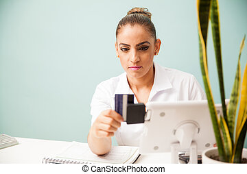 Payment with credit card in a spa - Female therapist and...