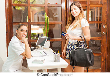 Paying with credit card at a spa - Profile view of a cute...