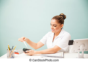 Cashier printing payment receipt at a spa - Happy female...