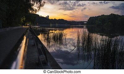 4K timelapse of summer evening park, river and concrete pedestrian embankment