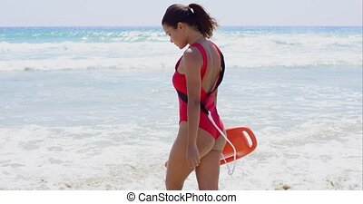 Female lifeguard steps into water on summer day while...