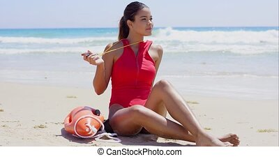 Pretty lifeguard sits on beach and twirls whistle as the...