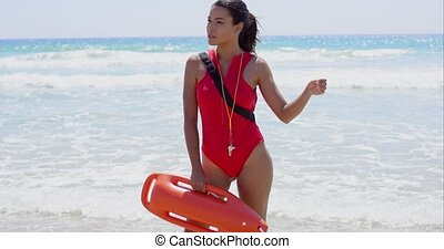 Young female lifeguard wearing red swim suit and holding a...