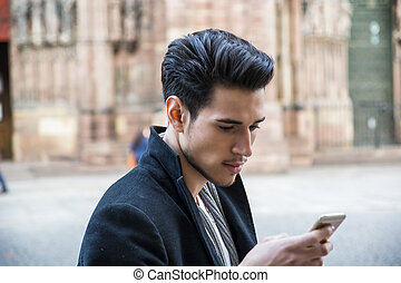 Young man in using cellphone outdoor in Europe - Young dark...