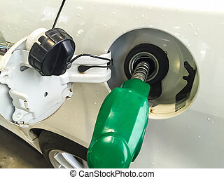 Refuel - Fuel pump nozzle in the fuel tank of a white car,...