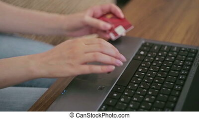 Woman shopping online at laptop with credit card