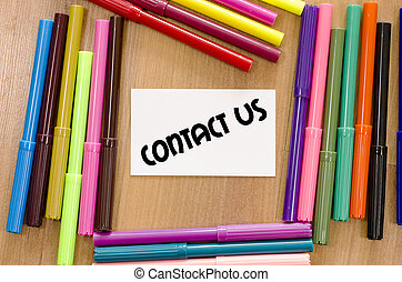 Contact us concept - Contact us written on memo over wooden...
