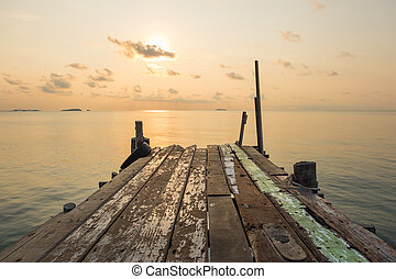 Wooden jetty bridge with tranquil scene of seascape during sunrise
